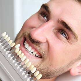 man comparing teeth to whitening chart