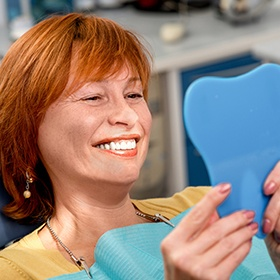 red haired woman smiling in mirror