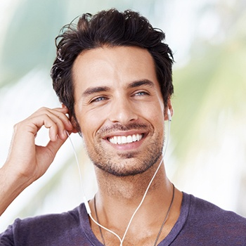 man smiling with headphones in