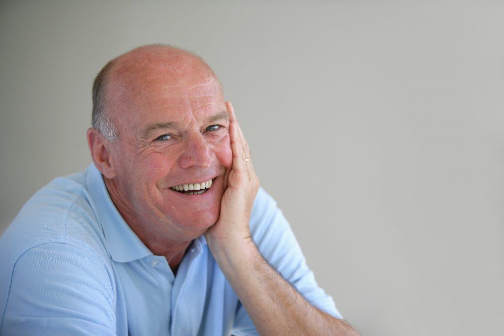 older man blue shirt smiling