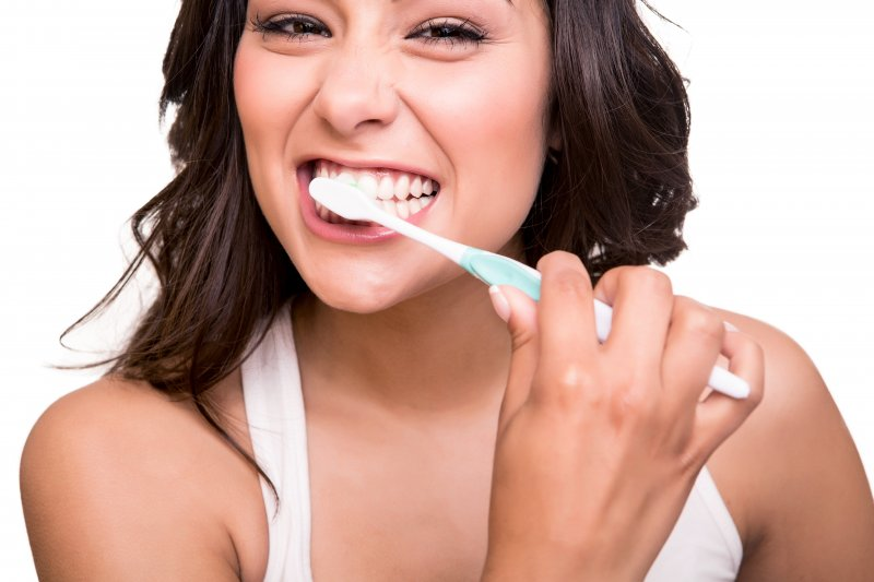 attractive woman brushing her teeth before visiting dentist in Lawrenceville