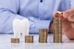 piles of coins for dental implants in Lawrenceville and model tooth