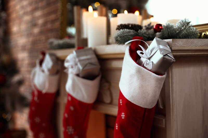 Stockings filled with gifts on fireplace