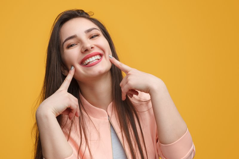 girl smiling and pointing to her smile